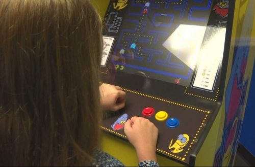 A young girl plays a Pacman arcade game