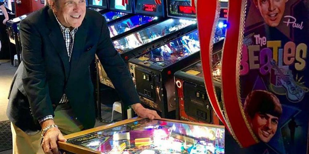 Man playing Beatles Pinball while Pinball Sales Soar In Retail's Shift to Online with Stern Pinball seeing sales surge on new machines f while new technology keeps old machines running.
