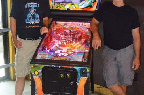 Jeff Murphy (L), who is hosting a four-strike pinball tournament at Noa Noa Sept. 11, and Scott Woods, owner of Noa Noa, pose with a Hot Wheels pinball machine Friday. A pinball machine just like the one pictured will be raffled off at the tournament. Photo by David Slone, Times-Union.